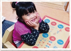 赤いジュニアデスクチェアに座り、デスクの上に頬杖をついてこちらを笑顔で見上げている女の子の写真。